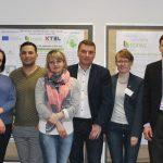 Gruppenbild der 13 Teilnehmer in einem Saal mit Plakaten zwischen ihnen Prof. Schlauderer