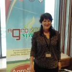 Dr. Bettina Fähnrich vor dem Aufsteller Agro Sym 2019