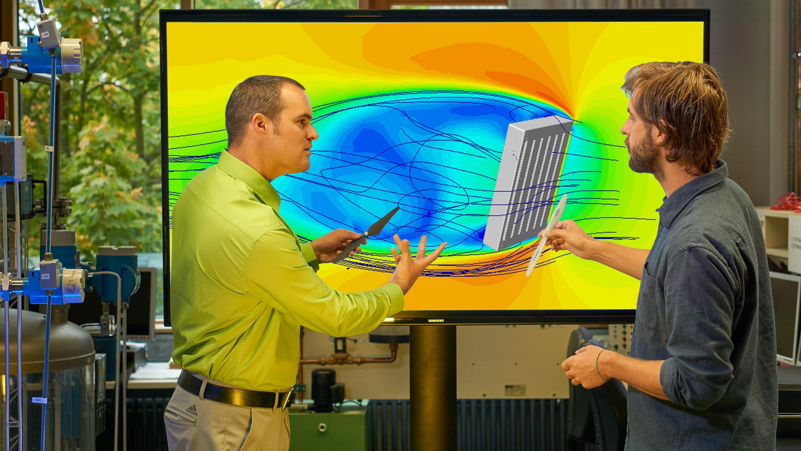 Die zwei Personen stehen vor einem einem Monitor auf welchem in verschiedenen Farben und Linien die Strömungen in einer Biogasanlage, die durch ein Rührwerk verursacht werden, dargestellt sind.
