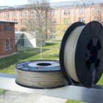 zwei Rollen auf denen durchsichtige runde Gummibänder aufgewickelt sind, im Hintergrund die Gebäude der Hochschule Ansbach