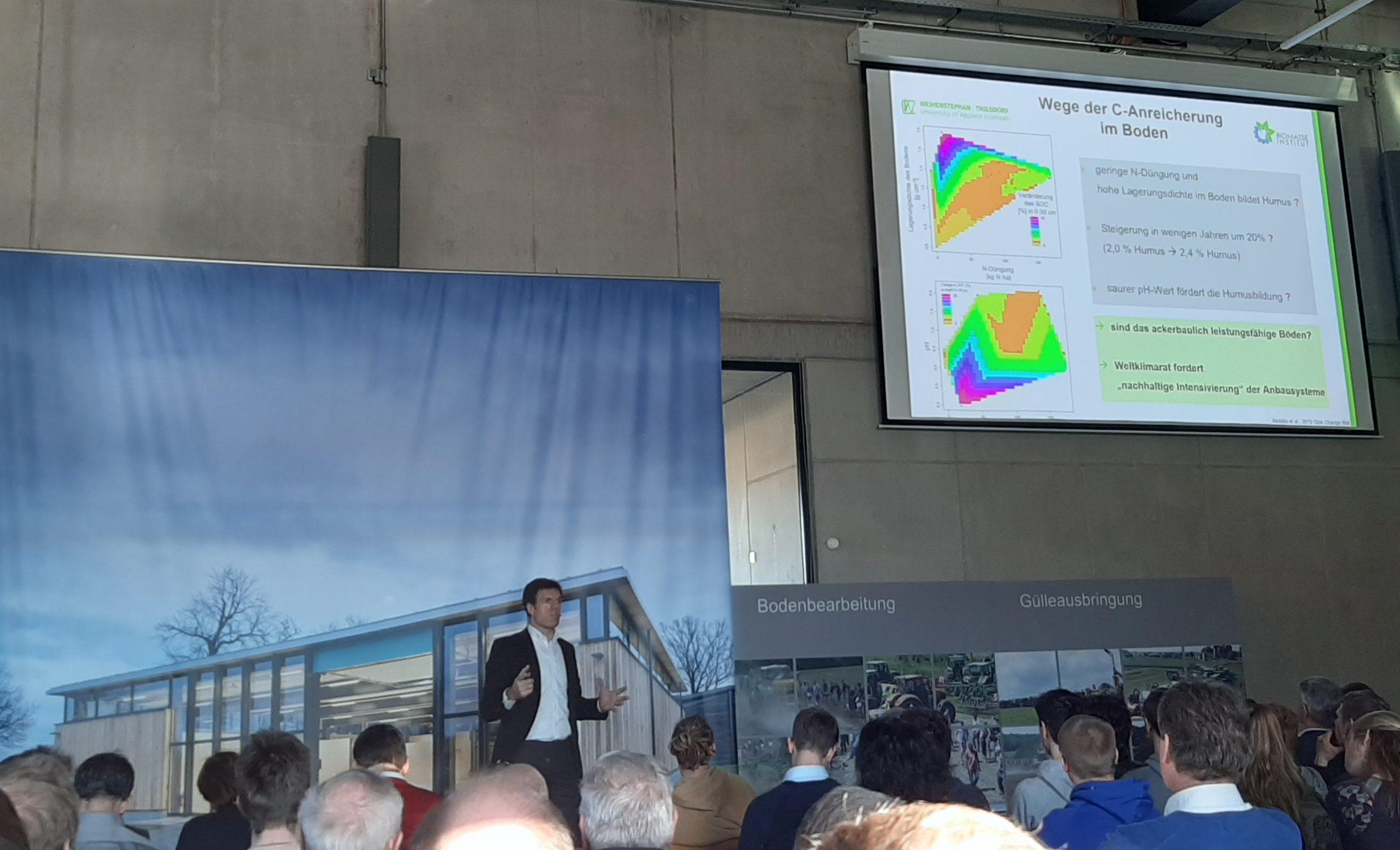 Prof. Dr. Bernhard Bauer während seines Vortrages, im Hintergrund auf einer Leinwand eine Folie zu Wege der C-Anreicherung im Boden seiner Präsentation