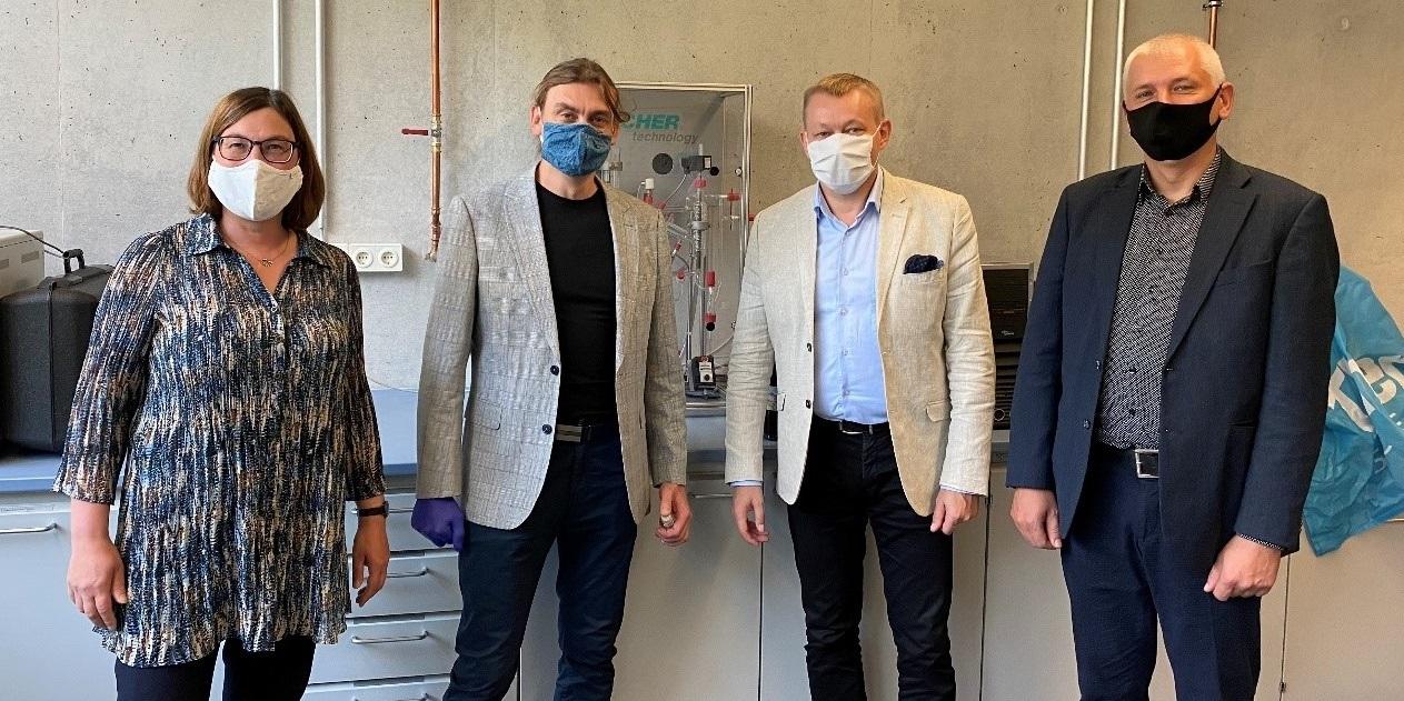 Die drei Männer und eine Frau haben eine Maske auf.