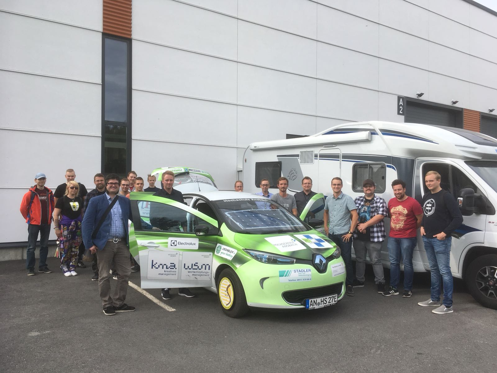 Um das grüne Forschungsauto aus Ansbach sind jede Menge Menschen (18) versammelt, die Türen vorne und der Kofferaum stehen offen