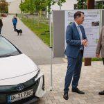 Dr. Gerd Müller mit Prof. Norbert Huber unterhalten sich neben dem Triobrid, dahinter ein Plakat zum Triobrid