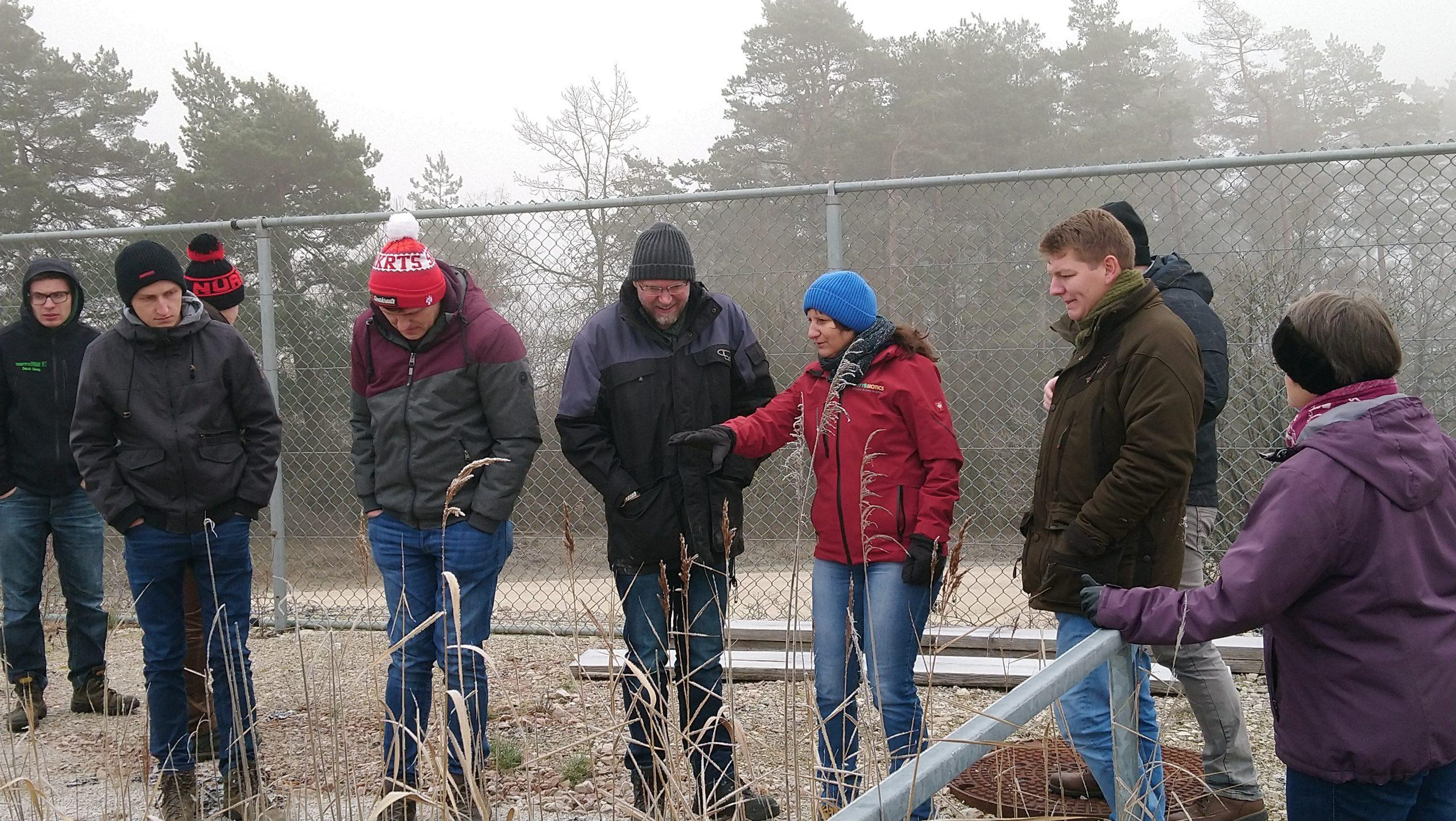 Die Dozentin erklärt etwas den außenrumstehenden Studenten, der Kleidung zur Folge scheint es Winter zu sein