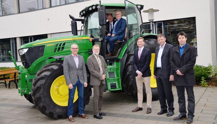 Zwei Personen sind im grünen Traktor, die weiteren fünf Personen stehen davor im Halbkreis