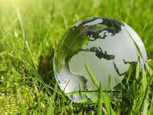 Weltkugel aus Glas mit Gras und Sonne