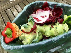 Frischer Biomüll mit Paprika und Kohl in einer kleinen Plastikschüssel
